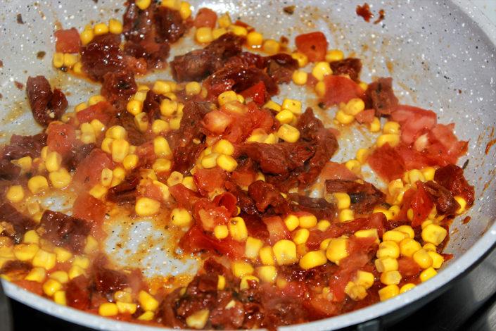 Getrocknetn Tomaten mit Mais in Pfanne